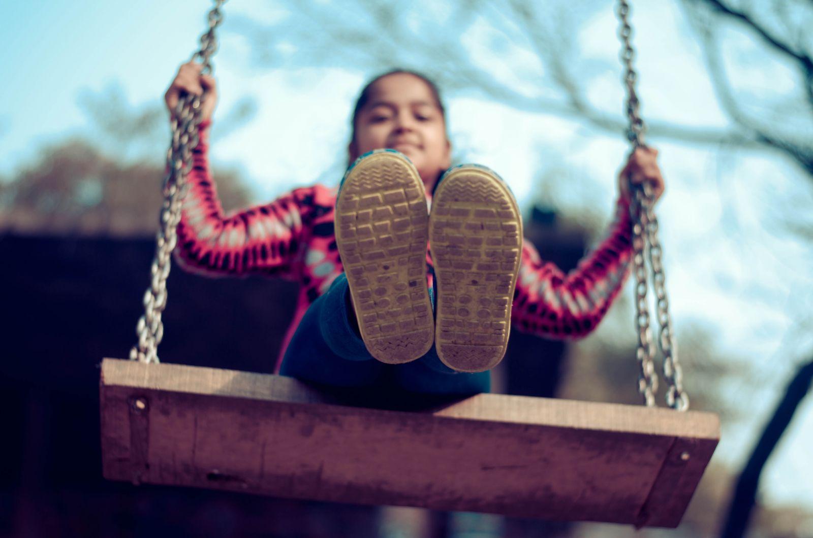 Meisje op houten schommel